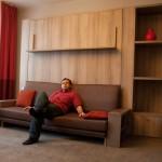 Узкий диван, много полочек и шкафчиков