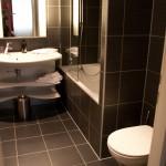 Санузел: ванна с душем, стильная раковина, встроенный фен, большой полотенцосушитель.
